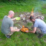Mit der Bratpfanne auf der Feuerstelle