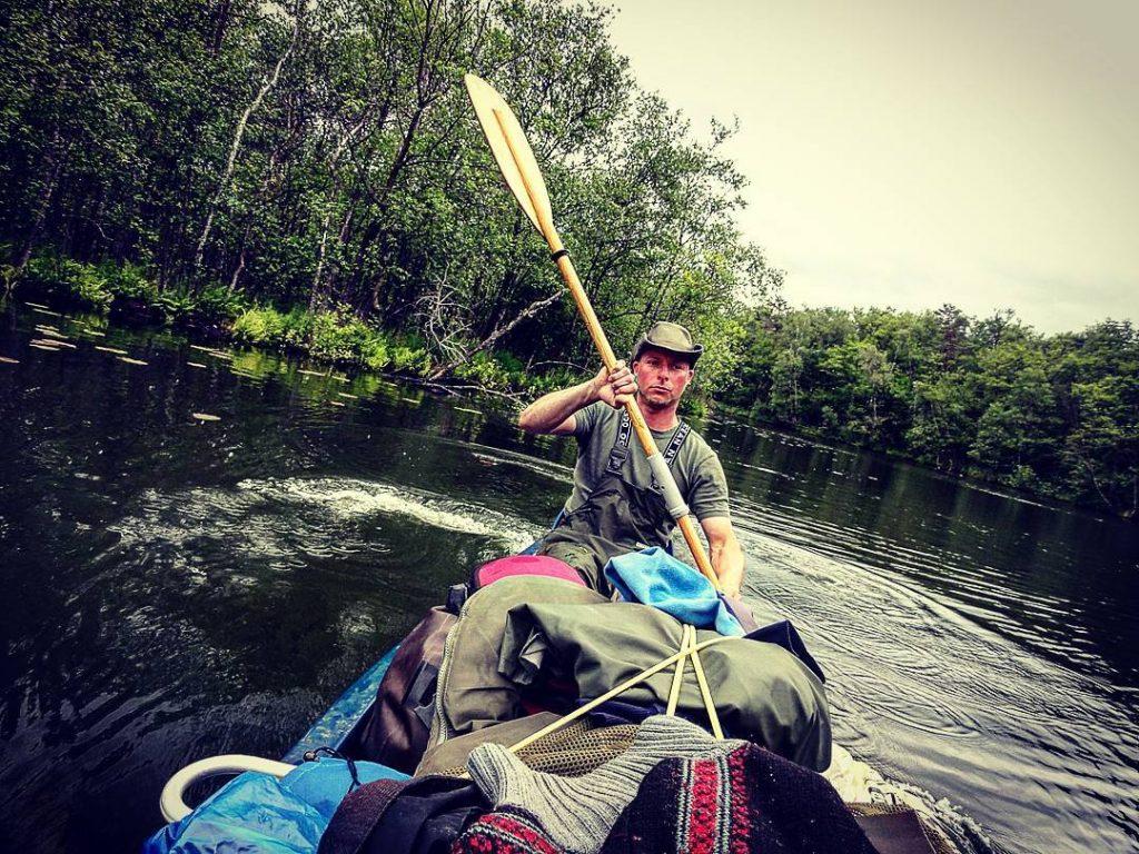 Auf dem Bild befindet sich eine Person beim Paddeln in einem Kanu. Im Kanu befindet sich viel Ausrüstung.