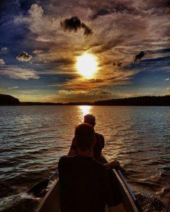 Auf dem Bild befinden sich zwei Paddler in einem Kanu die in den Sonnenuntergang paddeln.