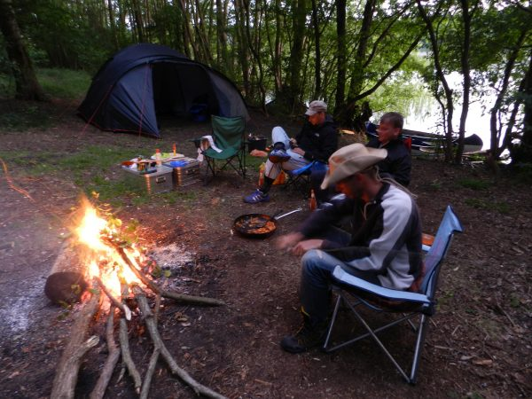 Auf dem Bild befinden sich mehrere Personen die an einem Feuer sitzen und essen. Es ist schon etwas dunkel und im Hintergrund befindet sich ein Zelt am Ufer eines Flusses.