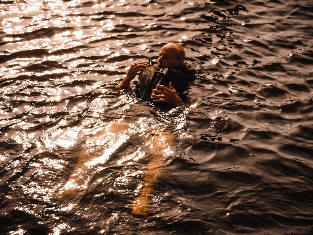 Auf dem Bild befindet sich eine Person die sich mit einer Schwimmweste bekleidet im Wasser treiben lässt.