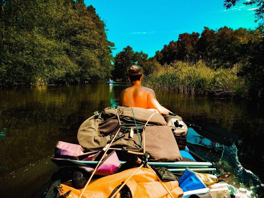 Auf dem Bild befindet sich eine Person die in einem Kanu vorne sitzt und paddelt. Das Bild wurde von der hinten sitzenden Person gemacht. Zusätzlich ist auf dem Bild viel Ausrüstung zu sehen, die auf dem Kanu verschnürt und gesichert ist.