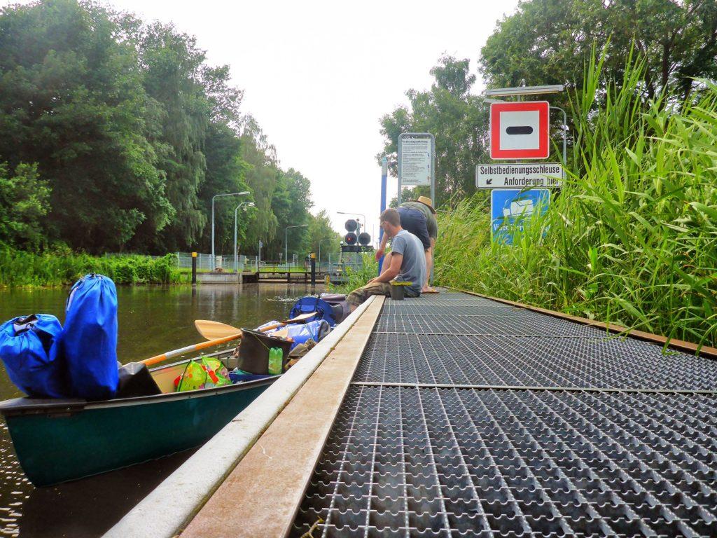 Auf dem Bild befinden sich zwei Personen im Wartebereich einer Schleuse. Eine Person ist damit beschäftigt das Kanu an einem Steg zu befestigen. Die andere Person schaut dabei zu. Das Schleusensignal leuchtet Rot. Es sind viele Hinweisschilder zu sehen.