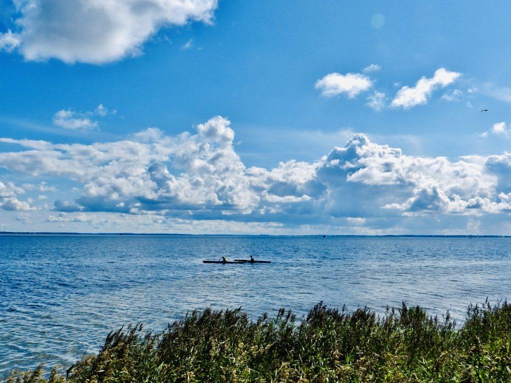 Auf dem Bild befinden sich zwei Paddler in Kajaks auf dem Strelasund und paddeln in Richtung der Insel Hiddensee. Am Horizont nur schwach zu erkennen, befindet sich das Festland der Insel Rügen. Im vordergrund des Bildes befindet sich der Silfgürtel neben der Badestelle in Barhöft.