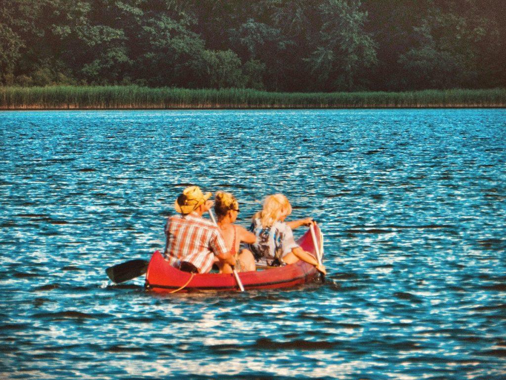 Auf dem Bild befinden sich drei Personen in einem Kanu auf einem See. Ein Mann mittleren Alters, sowie seine Frau und die Tochter der beiden. Dazu scheint die Sonne und der Mann trägt einen Cowboyhut.