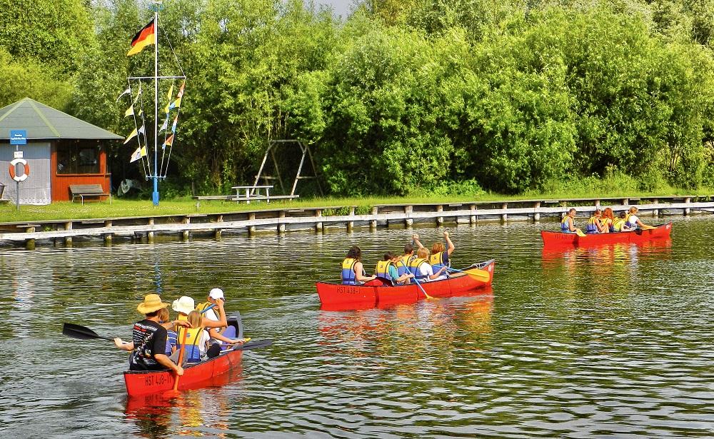 Eine Gruppe von Kindern die in drei Kanus mit jeweils einem Erwachsenen über den Fluss Paddeln