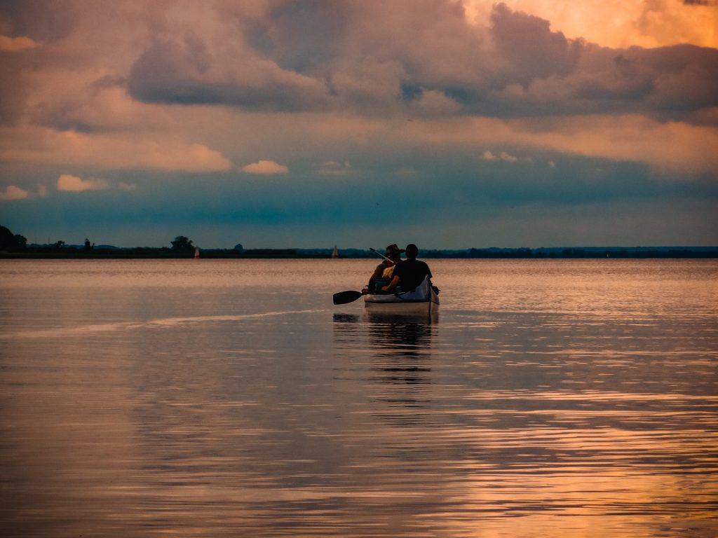 Auf dem Bild sind zwei Paddler in einem Kanu auf einem See unter einem schönen Abendhimmel.
