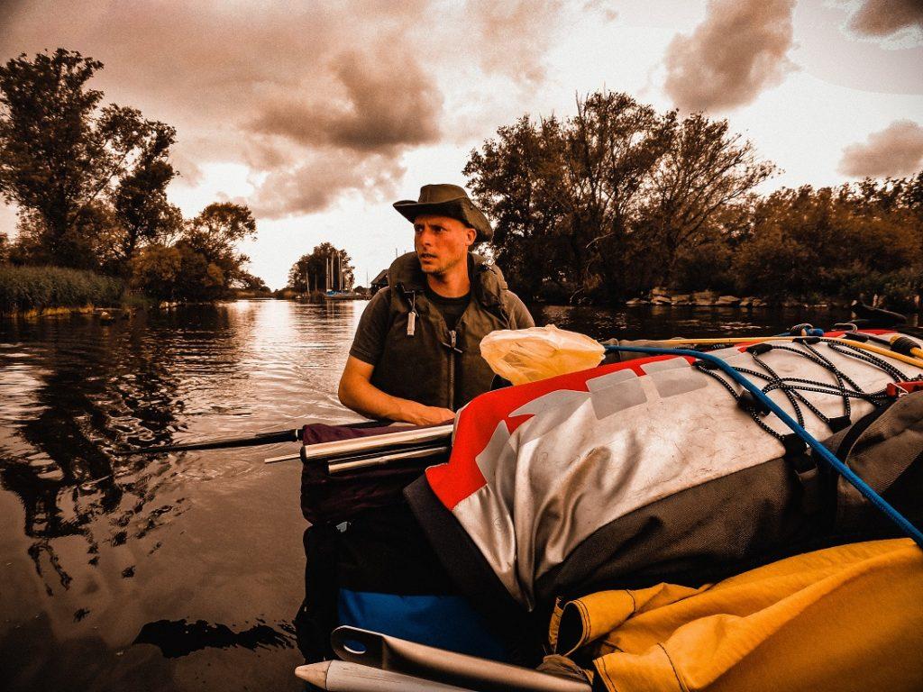 Auf dem Bild befindet sich ein Paddler der mit einem prüfenden Blick versucht die Wetterlage einzuschätzen.