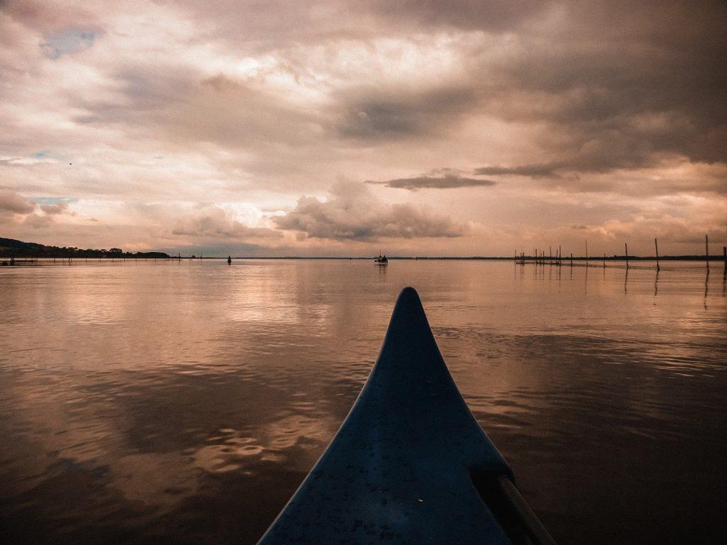 Auf dem Bild befindet sich eine Bootsspitze, ein stark bewölkter Himmel und ein großer See.
