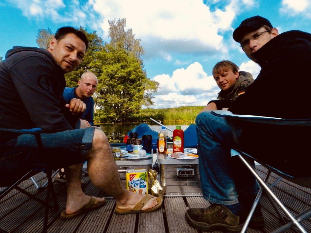 Auf dem Bild befinden sich vier Männer und Frühstücken auf einem Holzsteg direkt am Wasser.