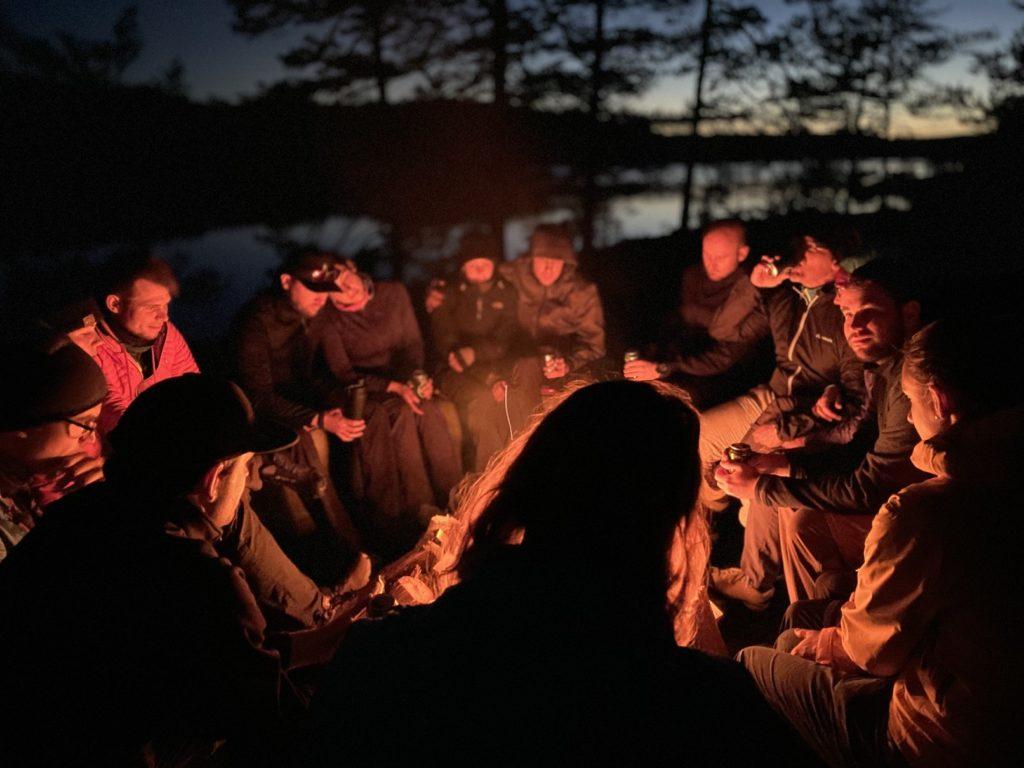 Auf dem Bild befinden sich mehrere Personen die inmitten der Natur im dunkeln um eine Lagerfeuer sitzen.