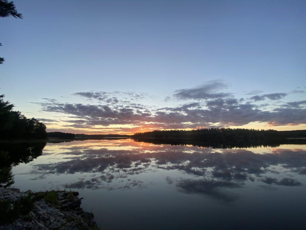 Auf dem Bild befindet sich ein See und am Horizont geht die Sonne unter. Der leicht bewölkte Himmel spiegelt sich im Wasser.