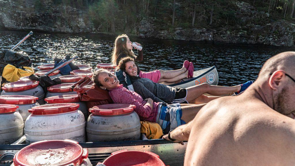 Auf dem Bild befinden siche mehrere junge Frauen die im Kanu gerade eine pause machen und fröhlich sind.