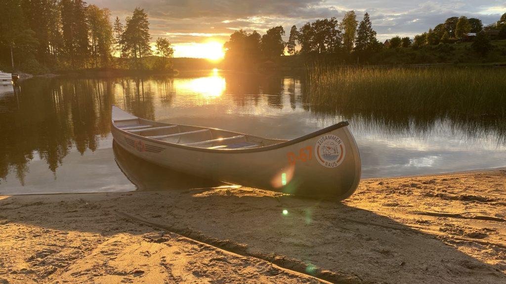 Auf dem Bild befindest sich im Vordergrund ein Kanu an einem Strand und im Hintergrund die Abendsonne die sich in einem See mit vielen Bäumen spiegelt.
