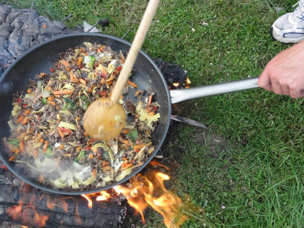 Auf dem Bild befindet sich eine Bratpfanne mit leckeren Zutaten gefüllt, die über dem offenen Feuer zubereitet werden.