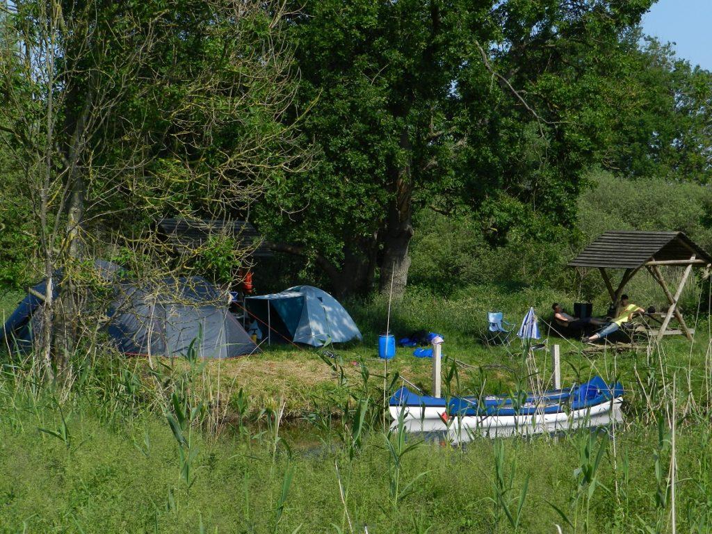 Auf dem Bild befindet sich ein Zeltlager direkt am Wasser in dem zwei Kanus an der Uferkante festgemacht sind.