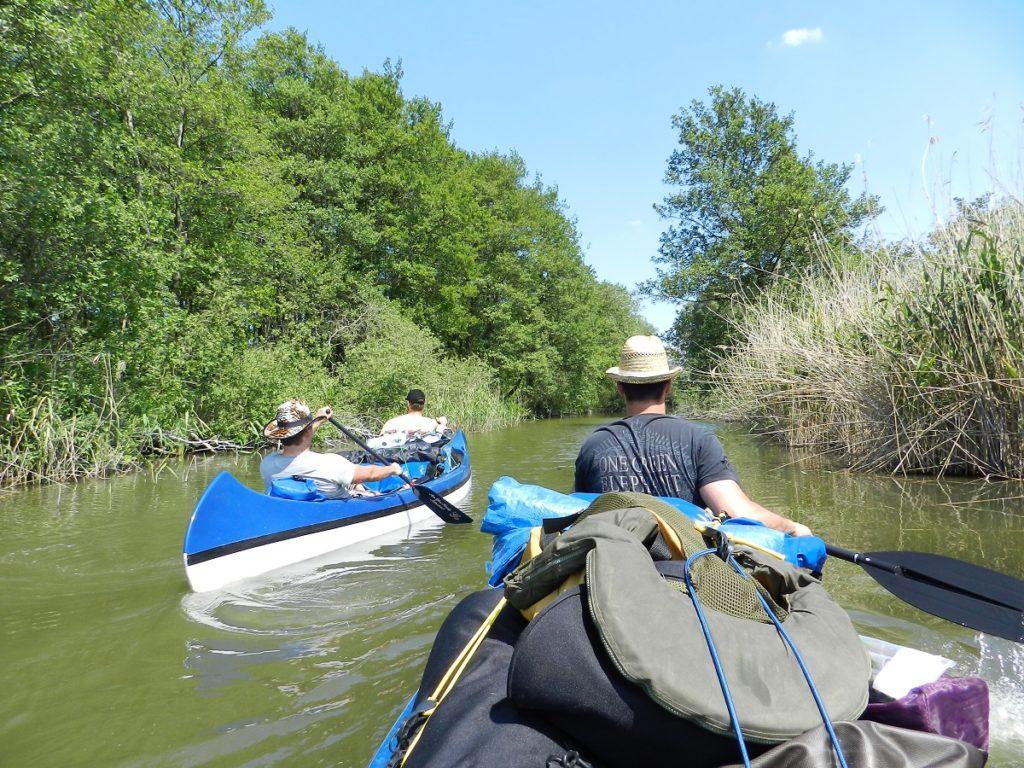 Auf dem Bild befinden sich mehrere Personen in zwei Kanus die durch einen schmalen Kanal paddeln.