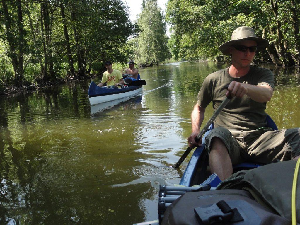Auf dem Bild befinden sich drei Personen in zwei Kanus inmitten einer natürlichen Wasserlandschaft.