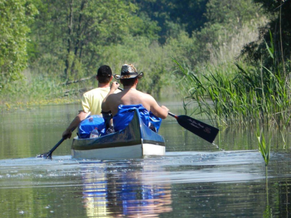 Auf dem Bild befinden sich zwei Personen die in einem Kanu einen schmalen Kanal entlang paddeln.