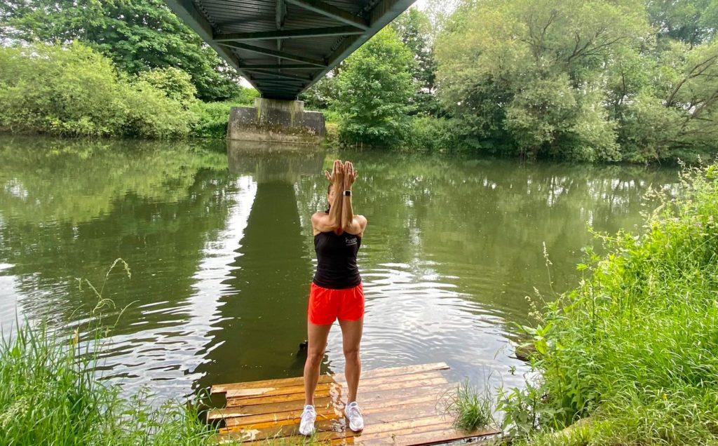 auf dem Bild befindet sich eine junge Frau die mit einer Übung zeigt, wie man die Schulterblätter mobilisiert.