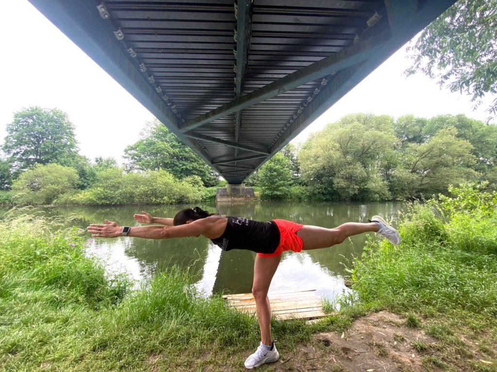 Auf dem Bild befindet sich eine junge Frau die mit einer Übung zeigt, wie die Standwaage funktioniert.