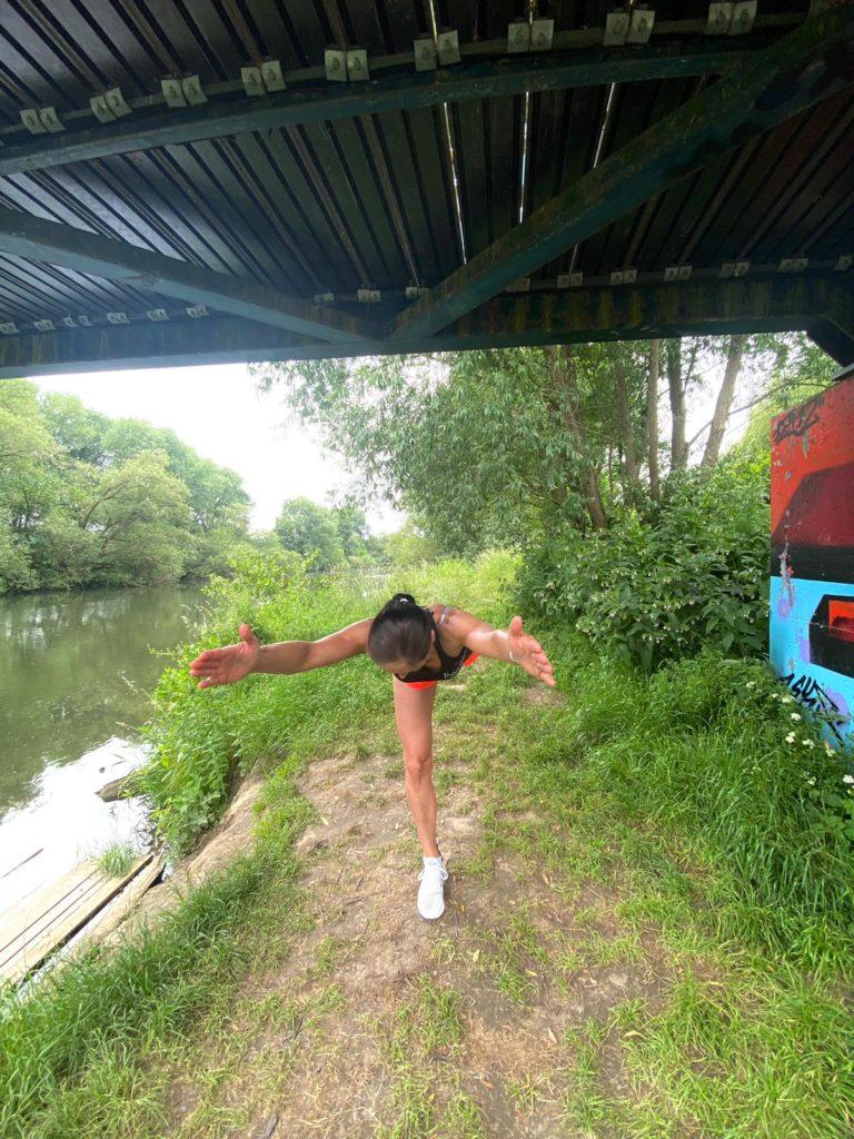 auf dem Bild befindet sich eine junge Frau die mit einer Übung zeigt, wie die Standwaage funktioniert